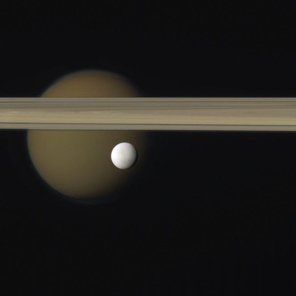Saturnove prstence, ľadový svet Enceladus s Titánom v pozadí
